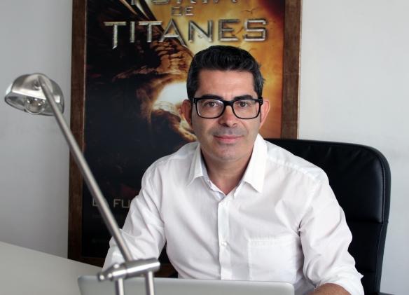 """Juan Cano, 'Nono', en su oficina de Adeje, frente al cartel de """"Furia de titanes"""" / SUR FILMS - OAC"""