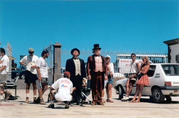 """Verano de 1996. Faro de Orchilla (El Hierro). Rodaje de """"La Raya"""" (Andrés M. Koppel). El entrevistado, Paco Rodríguez, es el segundo por la derecha, apoyado en el coche, junto a Cristina (maquilladora). El entrevistador, Luis Roca, es el segundo por la izquierda, con gorra verde y mirando unos apuntes en su bloc. A su derecha, Raúl García, auxiliar de cámara (hoy primer ayudante). De los actores, Bruto Pomeroy (i) interpretada al alcalde. En la secuencia intentaba hacer entrar en razón al torrero (Saturnino García) con ayuda del representante de la Reina de Inglaterra. / ARCHIVO LUIS ROCA"""
