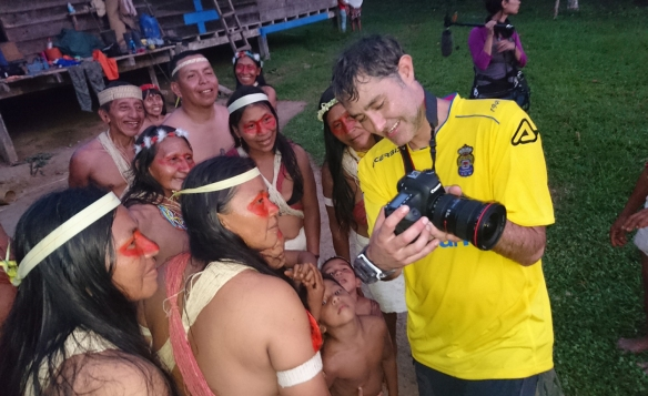 Manuel Cardenal muestra fotos a indígenas waoranis con la camiseta de la Unión Deportiva Las Palmas. / CATARATA FILMS