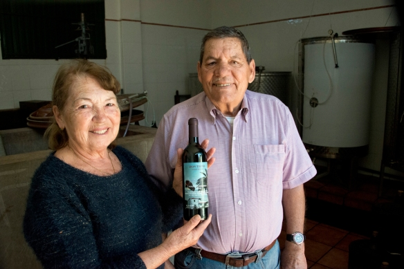 Don Trino con su mujer, que muestra orgullosa el vino premiado en el concurso local. Imprescindible probar la ropa vieja de Margarita. / LUIS ROCA ARENCIBIA